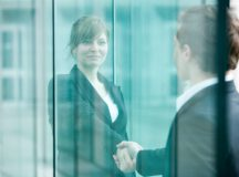 Businesswoman and businessman meet and shake hands at building entrance